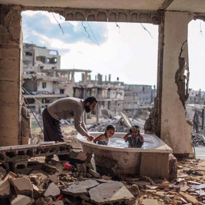 Palestinian father bathing his daughter and niece in their destroyed home